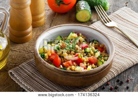 Delicious Israeli couscous Ptitim with vegetables on a table. Healthy vegetarian food for the meal. Traditional Moroccan cuisine. Top view.