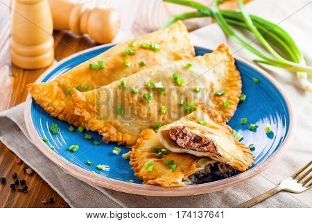 Chebureki with meat and spring onion. National Russian Turkish Ukrainian Tatar and Romanian food on a table. Middle East traditional meat pastry.