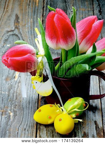 Bunch of Magenta Tulips in Watering Can with Colored Easter Eggs and Handmade Chicken Figure closeup on Rustic Wooden background