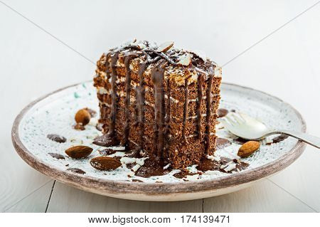Piece of chocolate Spartak cake on a table. Delicious sweet food on a beautiful plate. Close-up shot.