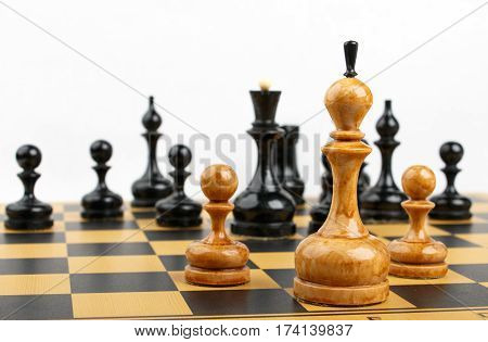 white chess king and two pawns opposite the black figures