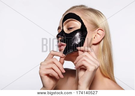 A young girl takes a black mask from her face. The gray background.