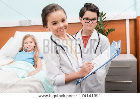 Kids with stethoscopes playing doctors near little patient lying in hospital bed