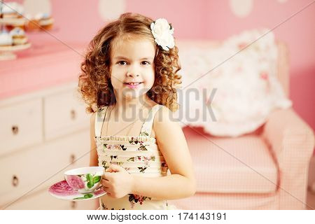 Little cute girl in a pink dress drinks tea with sweets in the children's room. Baby with curls hairstyle play in the nursery. Positive child and tea party