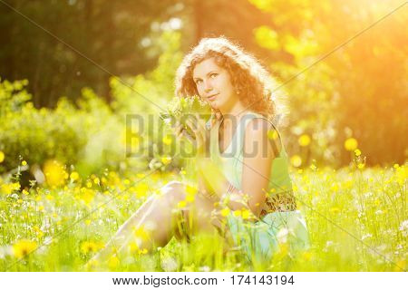 Young spring or summer fashion woman  in blowing garden spring landscape background. Springtime or summertime. Trendy girl at sunset. Allergic to pollen of flowers. Spring allergy