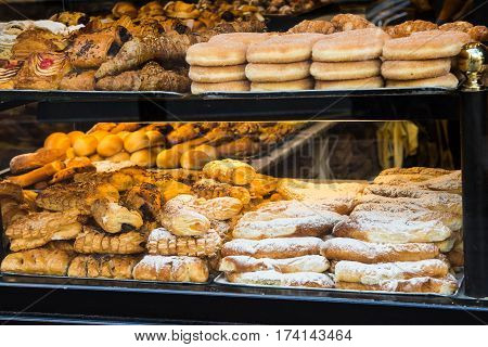 Display window of a bakery and pastry shop of a European city with variety of baked goods breads donuts puff pastry closeup Alicante Spain