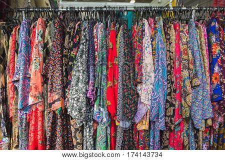 Close up colourful clothes hang on clothes rack in clothing store, horizontal