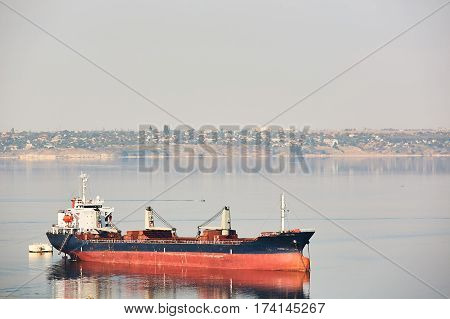 Empty bulk carrier cargo ship with deck cranes sailing on a river calm water