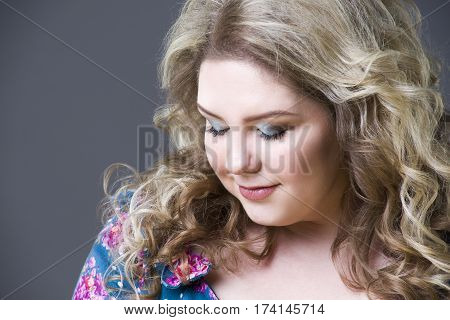 Young beautiful happy blonde plus size model in dres xxl woman portrait on gray studio background makeup and hairstyle
