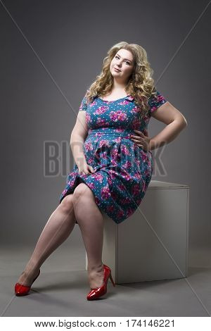 Young beautiful happy blonde plus size model in dress and shoes xxl woman on gray studio background full length portrait
