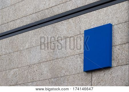 Horizontal side view of empty square blue signage on business building covered in marble