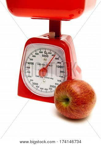 red apple and kitchen scales on a white background. vertical photo.