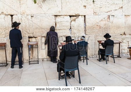 The Western wall or Wailing wall in the old city of Jerusalem, Israel. Jews in traditional attire pray at the wall of the temple.