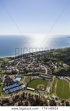 Aerial view of homes, streets, ball fields and pacific ocean horizon in Malibu, California.