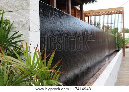 Waterfall cascading over black tile lined with palms.