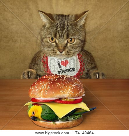 The hungry cat is sitting at a table. He is going to eat a delicious bird burger. This cat is a fan of silence.