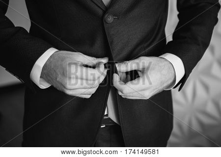 Black and white art photography monochrome man buttoning his waistcoat on. Men's style. Professions. Preparing to work on an appointment.