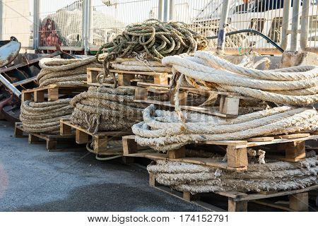 Stack of rolled mooring lines on timber pallets in a fishing port boat nets in the background Mediterranean sea Costa Blanca Spain closeup