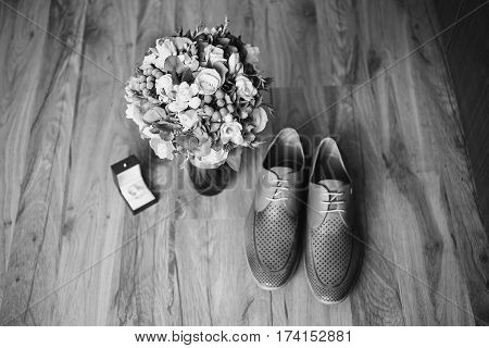 Black and white art photography monochrome gray man's shoes on the floor. Men's style fashion. Charges groom. Wedding bouquet rings lie on a wooden background.