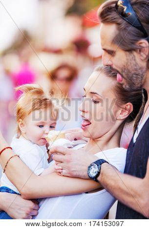Mother and a father are hugging a baby boy and feeding him with ice cream outdoors. Copy space.