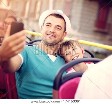 Father with his son traveling by tour bus and taking selfie