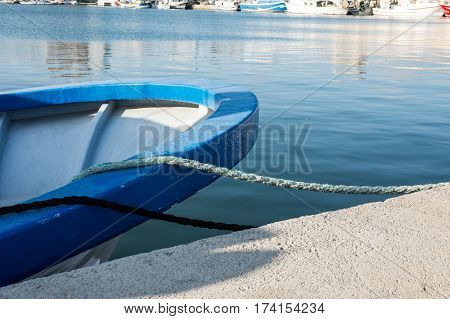 Stern of a blue fishing boat docked in port tied with mooring lines waterfront sunny day closeup yachts in the background