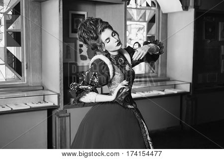 Black and white art photography monochrome girl with blue eyes in red dress. Queen with a high hairdo. Vintage image. A woman with pale skin