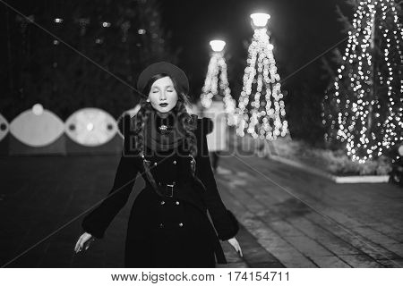 Black and white art photography monochrome girl with beret and scarf standing against the background of the Christmas tree. Coloured bokeh. Abstract background. Golden garland. New year's night. Cold evening. Art