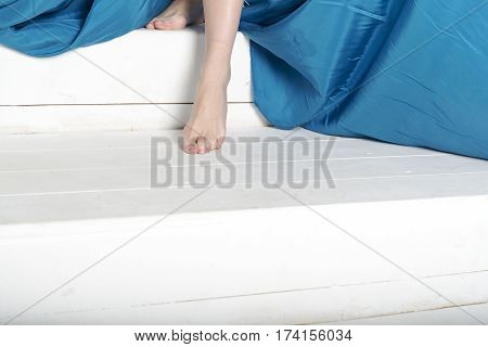 Female feet on a white background and a blue cloth.