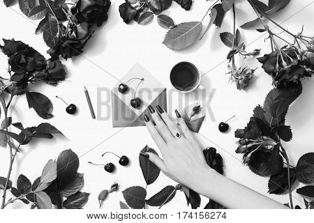 Black and white art photography monochrome woman's hand with nails with a silver ring with black stone corundum and rim theon. Tea small envelopes with green leaves roses lay on white background