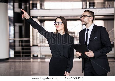 Young businesswoman showing something to businessman seen through glass