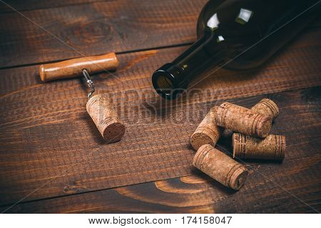 Bottle Of Red Wine, Corkscrew And Corks On Wooden Table