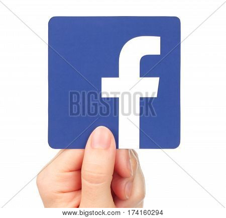 Kiev Ukraine - January 20 2016: Hand holds Facebook icon printed on paper. Facebook is a well-known social networking service