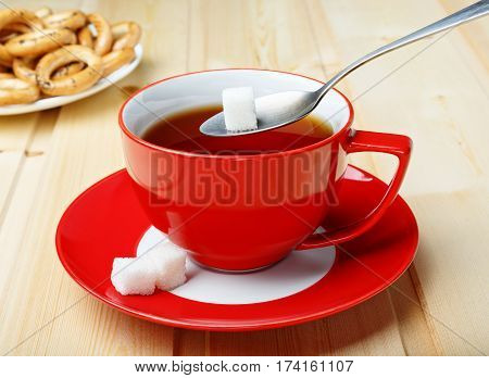 A cup with sugar on a spoon red mug with tea on a wooden background over a cup spoon with refined sugar sugar.