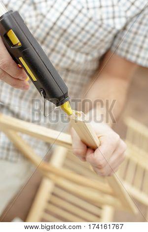 Man putting an electric hot glue gun on wood furniture close-up