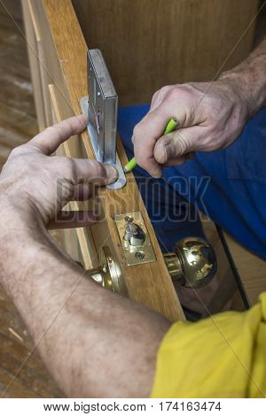 Carpenter doing on old wooden door the markup for the mortise lock using a pencil.