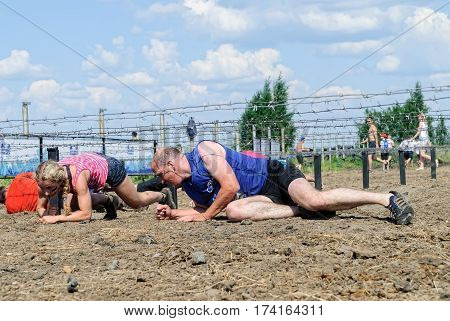 Tyumen Russia - July 9 2016: Steel Character extrim race on Voronino Hill. Army Test. People jumping crawlingpassing under a barbed wires or climbing obstacles during extreme obstacle race