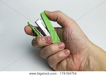 Hand on a white background holding a stapler for paper.