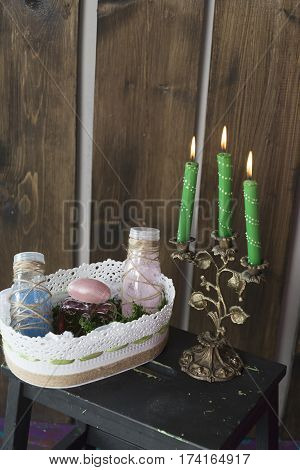 Candle holder with three lit candles on the table.