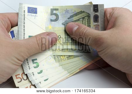 Hands holding a wad of cash on a white background.