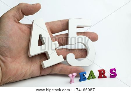 Hand holds a number forty-five on a white background.