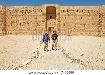 AMMAN, JORDAN - AUGUST 23 2012: Unidentified people visit desert castle Qasr Kharana (Kharanah or Harrana) near Amman, Jordan. Built in 8th century used as caravanserai.