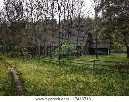 Wooden house in  forest . Country house . Cottage behind a wooden fence in the trees.