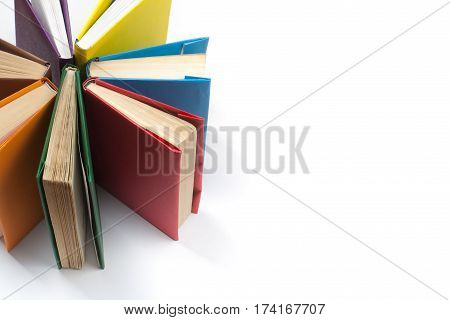 Top view of colorful hardback books in a circle. Open book fanned pages. Back to school copy space. Education background
