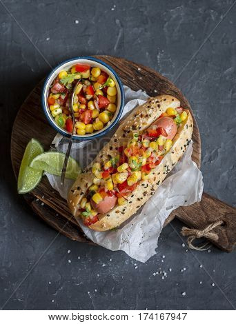 Mexican street style hot dog with corn salsa on a wooden cutting board on dark background top view