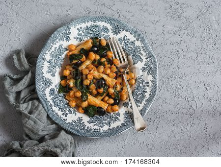 Vegetarian rigatoni pasta with chickpeas spinach and olives in a tomato sauce on a light background top view.