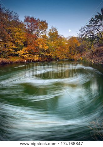 Moonrise over the Autumn river with whirlpool