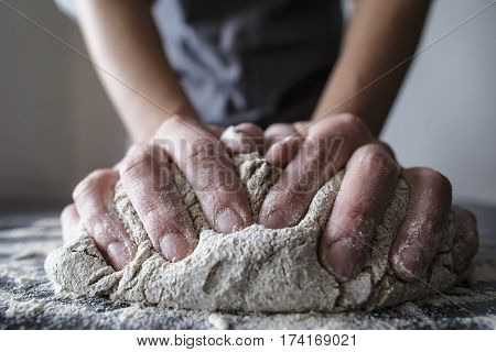 close-up of human hands in the apron knead the dough on a black wooden table sprinkle with flour