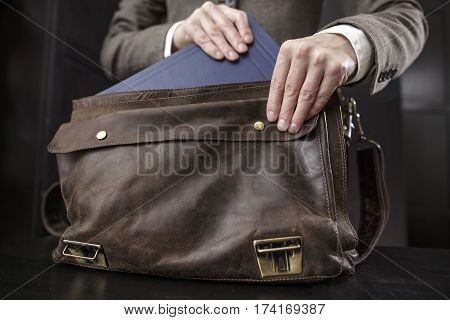 teacher in a jacket gets a book from an old leather briefcase standing on a table in the audience