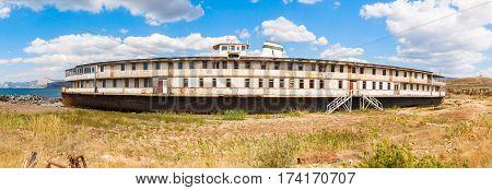 old rusty wheel steamship on the sea shore in Crimea